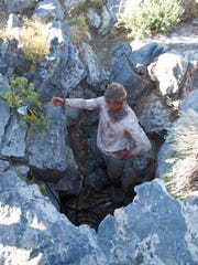 A rescuer stands in the mouth of a cave where St. George