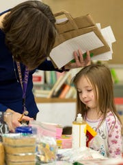 Londa Kuehn helps Molly Humphrey, four, pick out gifts on her list as Pittsville Elementary hosts an open store for students to purchase gifts for their loved ones for the holidays on December 6, 2016, and in return, the money will be matched by a unanimous donor. The proceeds will be given to the food pantry at St. John's Lutheran Church in Pittsville, Wisconsin.