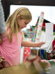 Ashley Fox, seven, clutches her bag full of gifts and takes it to the cash register as Pittsville Elementary hosts an open store for students to purchase gifts for their loved ones for the holidays on December 6, 2016, and in return, the money will be matched by a unanimous donor. The proceeds will be given to the food pantry at St. John's Lutheran Church in Pittsville, Wisconsin.