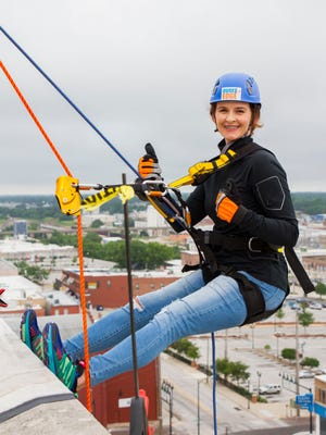 Allison Cash, a 2016 participant  in Over the Eedge, rappels down the side of the Sky Eleven building.