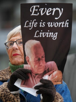 Margie Montgomery of Kentucky Right to Life holds a sign during an anti-abortion rally in front of Metro Hall, in Louisville. Jan. 23, 2017