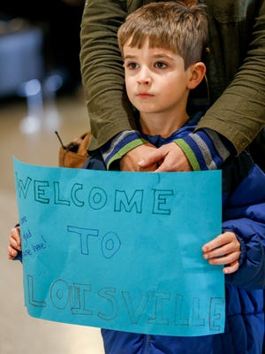 Leo Hillis, 5, holds a sign welcoming a family from the Democratic Republic of Congo as they arrive at the Louisville airport Thursday afternoon. They may be the last group of refugees that is allowed in to at the Louisville airport per the immigration ban. Feb. 2, 2017