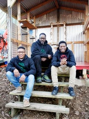 From left, Devin Jones, 18, DeWayne Barton, founder of Hood Huggers, and Donovan Spencer, 15, in a Hood Huggers Peace Garden February 1, 2017.