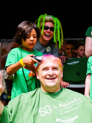 Princeton Bryan, now 7, shaves his doctors head at St. Baldrick's Foundation's big event last year at The Avenue Viera.