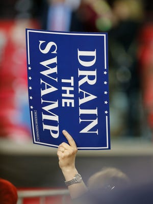 Aw woman waved a Drain the Swamp sign during President Donald Trump's visit to Freedom Hqall in Louisville. March 20, 2017.