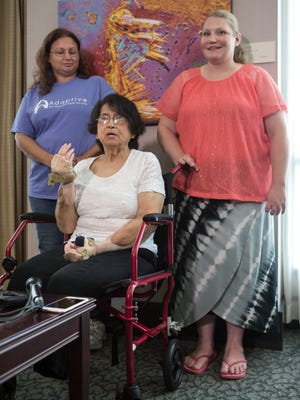 Louella Aker, center, spoke to the media on the one year anniversary of her double hand transplant. With her are Laurie Carter, left, and Susie Davis, who help with her care. Sept 19, 2017.