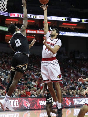 U of L's Anas Mahmoud puts up a shot over Bryant's Brandon Carroll during the first half of play against the visiting Bryant Bulldogs at the KFC Yum! Center on Monday night. Dec. 11, 2017