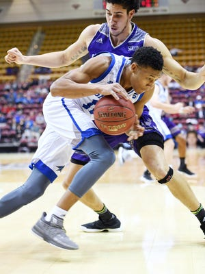 UNC Asheville's Raekwon Miller is guarded by Western Carolina's Marc Gosselin December 17, 2017 at the US Cellular Center in Asheville.