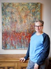 """Mary Farmer, an encaustic painter, stands next to one of her paintings, titled, """"Keepers Find it Within"""" in her home in South Asheville January 12, 2018. Encaustic painting is an ancient form of painting with layers of beeswax and colored pigments."""