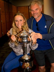 In this photo released by Tennis Australia, Denmark's Caroline Wozniacki and her father Piotr pose for a photo with the Daphne Akhurst Memorial Cup after winning the women's singles final against Romania's Simona Halep at the Australian Open tennis championships in Melbourne, Australia, Sunday, Jan. 28, 2018. (Fiona Hamilton/Tennis Australia via AP)