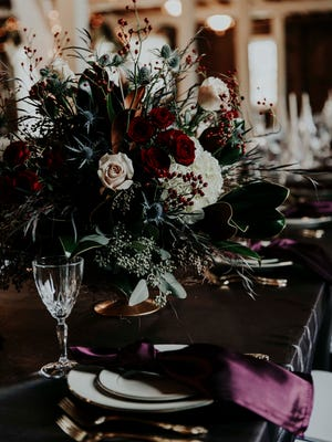 Red and white flowers make up a centerpiece at a Delaware County wedding venue.