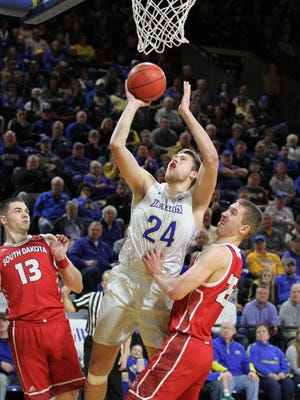 South Dakota State's Mike Daum (24) scores in the paint against South Dakota's Matt Mooney (left) and Tyler Hagedorn during the second half of the Jackrabbits' 76-72 victory over the Coyotes Thursday night at Frost Arena.