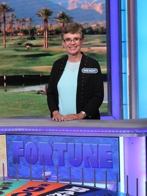 """Wendy Quinlan, of Port St. Lucie, stands at the wheel during a taping of """"Wheel of Fortune."""""""