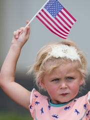 Piper Sikkema waves a flag as Kentucky Air National Guardsmen return home at the Kentucky National Guard Base in Louisville, Kentucky on Wednesday. July 4, 2018