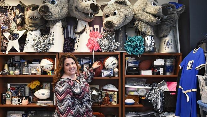 Nevada cheerlearder coach Kim Anastassatos stands next to souvenirs in her office. Anastassatos is a driving force behind the Wolf Pack's altruism.