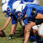 Players line up for the snap during spring football practice at Titusville High School.