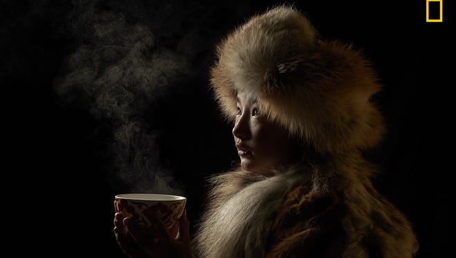 "People, first place: ""Tea Culture"" by Alessandra Meniconzi. ""For a long time, I have been fascinated by the ancient Mongolian method of hunting with Golden Eagles. In early 2018, I followed one family of eagle hunters during their migration from winter camp to spring camp. Mongolia is sparsely populated, but the inhabitants have a very hospitable and welcoming culture. Tea for Kazakh culture is one of the attributes of hospitality. Tea isn't just a drink, but a mix of tradition, culture, relaxation, ceremony, and pleasure. Damel, seen here wrapped in heavy fur clothes, drinks a cup of tea to keep warm from the chilly temperatures in Western Mongolia."""