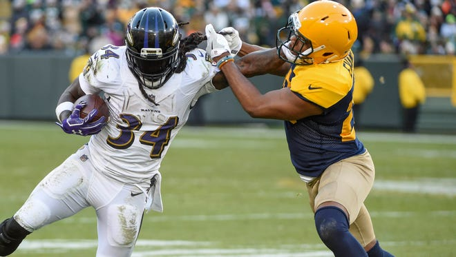 Baltimore Ravens running back Alex Collins tries to break a tackle by Green Bay Packers safety Marwin Evans in the fourth quarter at Lambeau Field.