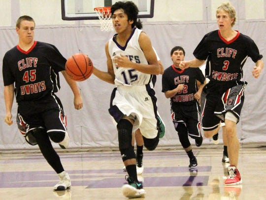 Mescalero's Matias Lapaz, center, brings the ball down the court on a fast-break Friday night.