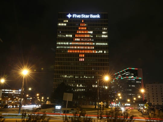 Five Star Bank Plaza on Chestnut Street lights its office windows in the shape of a giant red Christmas tree, visible on two of the four sides of the tower.