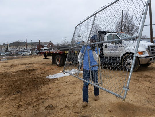 Federal Rent A Fence employee Shaun Lee carries a section