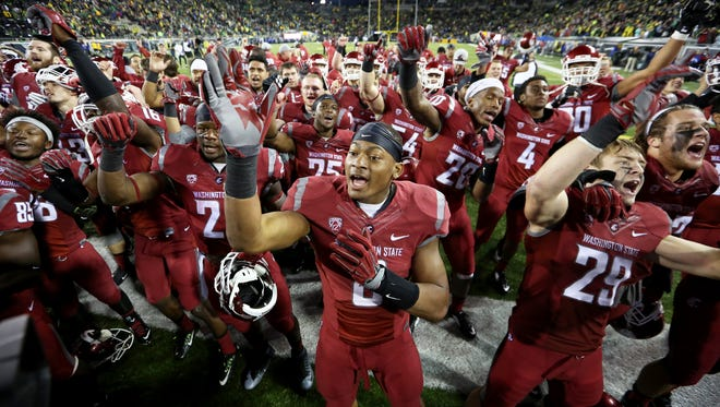 The Washington State football team celebrates after an NCAA college football game against Oregon, Saturday, Oct. 10, 2015, in Eugene, Ore. Washington State won 45-38 in overtime.