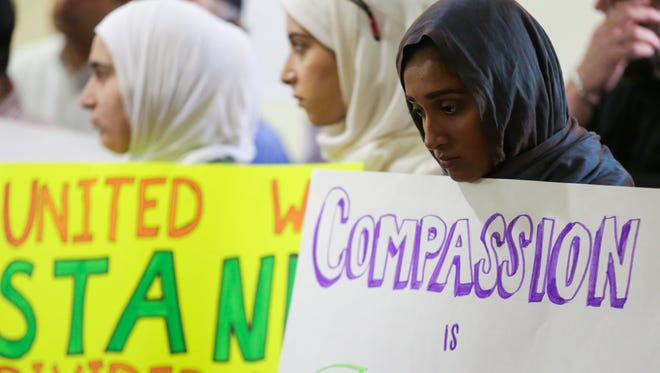 Huda Kutmah, from left, Ayah Kutmah and Zoha Mian hold signs for peace during the interfaith prayer vigil held at the Louisville Islamic Center in light of the tragic events in Nice, France. July 15, 2016