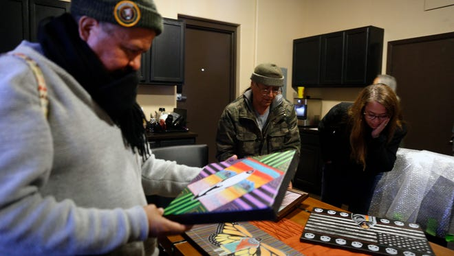 Artist look over each other's work on Tuesday, Feb. 20, 2018 at the Capacity Builders offices in Farmington.
