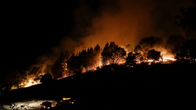 Firefighters watch from their fire trucks as wildfires continue to burn  Oct. 12, 2017, near Calistoga, Calif.