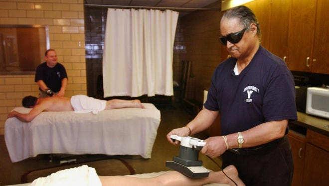 Massage therapists Larry Boyd, left, and Bob Mickle work on clients at the YMCA in 2003. The men were called into a meeting on April 9 and told they no longer had a position.