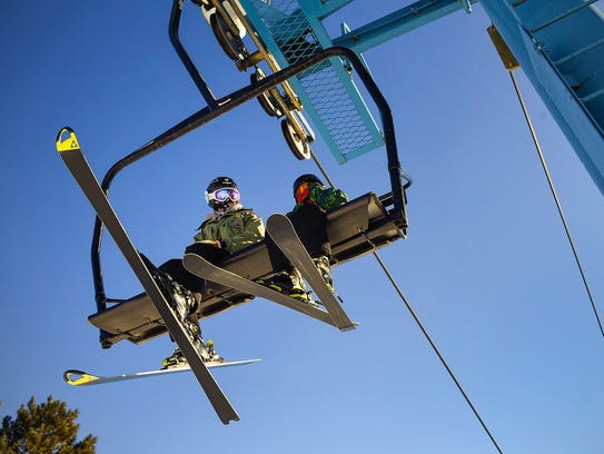 Skiers ride the chairlift Saturday, Dec. 30, at Powder