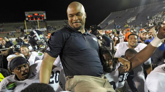 Former Auburn player and coach Dell McGee, shown here being carried off the field by Georgia Southern players after a 58-27 victory in the GoDaddy Bowl in Mobile, Ala., on Dec. 23.
