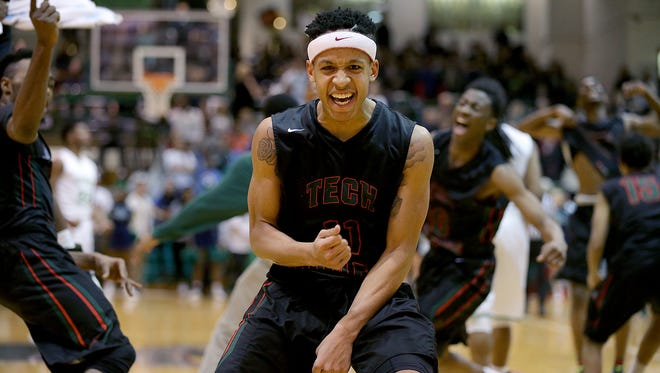 Arsenal Tech Titan CJ Walker (11) begins to celebrates their win in the Indianapolis City Boys Basketball Tournament finals Monday, Jan 25, 2016, evening at Arsenal Tech High School. The Asenal Tech Titan defeated the Cathedral Irish 60-55.