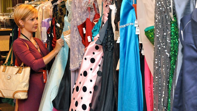 Lisa Spooner looks through the dress selection at the Embassy Suites during Love That Dress! 2015. The event raises funds for PACE Center for Girls.