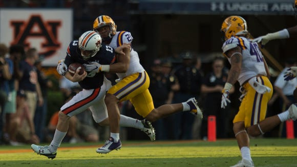LSU cornerback Ed Paris (21) tackles Auburn quarterback Sean White (13) during NCAA football game between Auburn and LSU Saturday, Sept. 24, 2016, at Jordan Hare Stadium in Auburn, Ala.