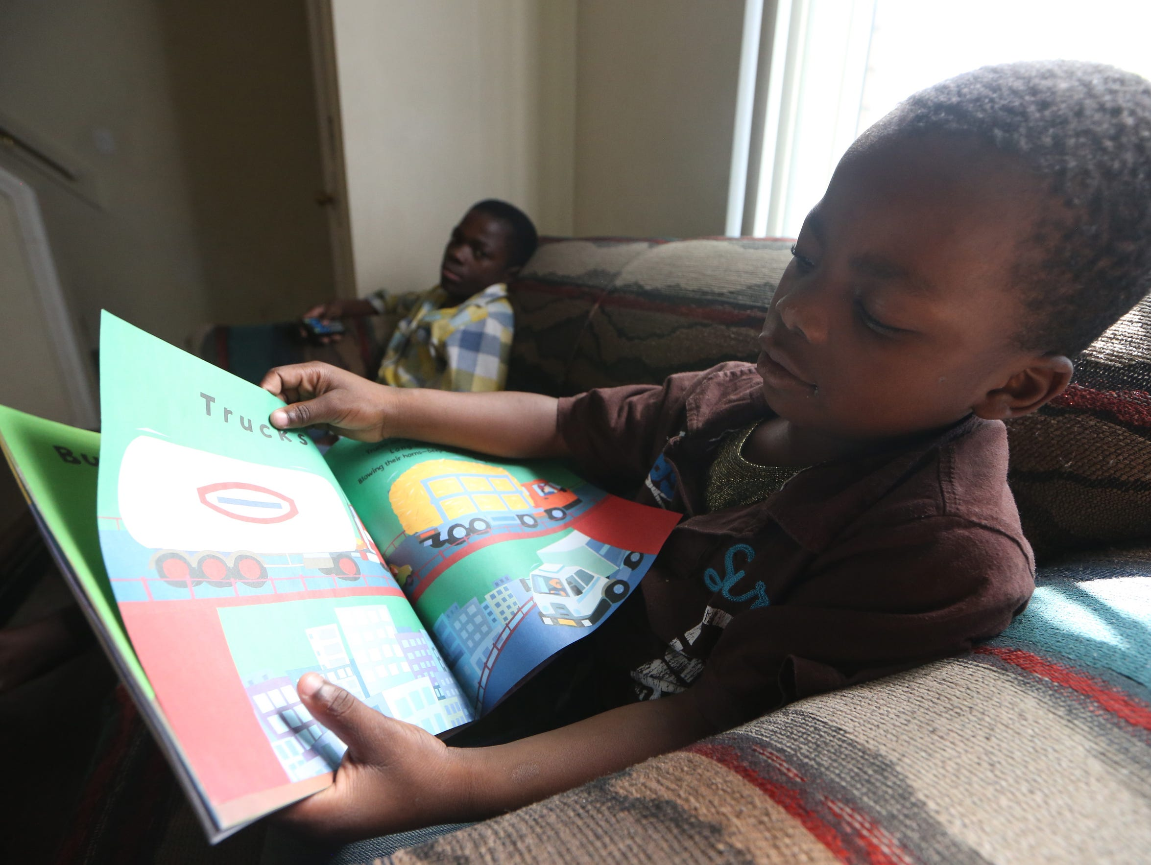 Abdineko, 7, looks over his book at their home a month