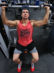 Michael Dubree performs seated presses at Powerhouse