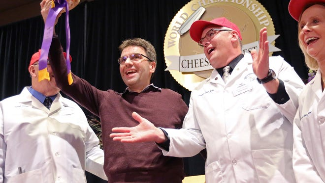 Sylvain Diedrichs, a representative of Savencia Cheese USA of New Holland, PA., holds the Best in Show winner during the finals of the World Championship Cheese Contest at Monona Terrace in Madison, WI., Thursday, March 8, 2018. The hard sheep's milk variety called Esquirrou bested 19 other finalists on the final day of the three day event. The contest, hosted by the Wisconsin Cheese Makers Association, is the largest technical cheese contest in the world and this year drew a record 3,402 entries to 121 categories.
