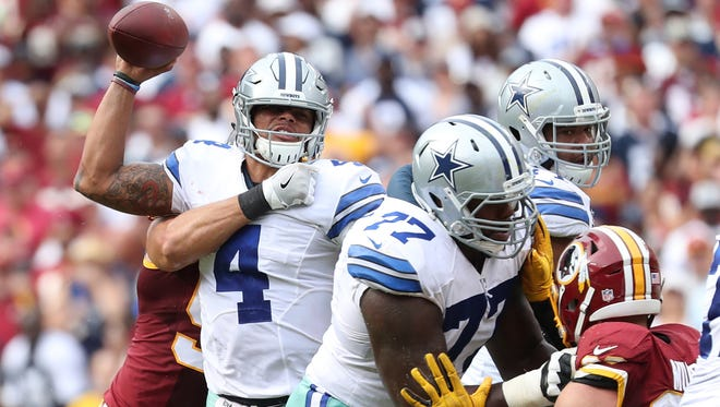 Dallas Cowboys quarterback Dak Prescott (4) throws the ball while being tackled by Washington Redskins linebacker Ryan Kerrigan (91) in the fourth quarter at FedEx Field. The Cowboys won 27-23.