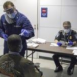 A photograph made available by US Customs and Border Protection on Oct. 17, 2014, shows a member of the US Coast Guard, upper left, taking the temperature of an arriving passenger, as a Customs officer examines documents during screening for the Ebola virus at O'Hare International Airport in Chicago, Ill.