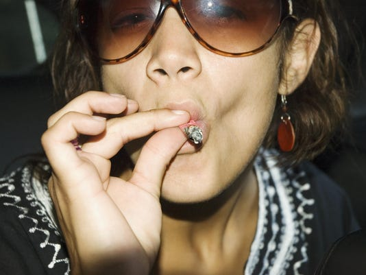 Close-up of young woman in sunglasses smoking a marijuana joint