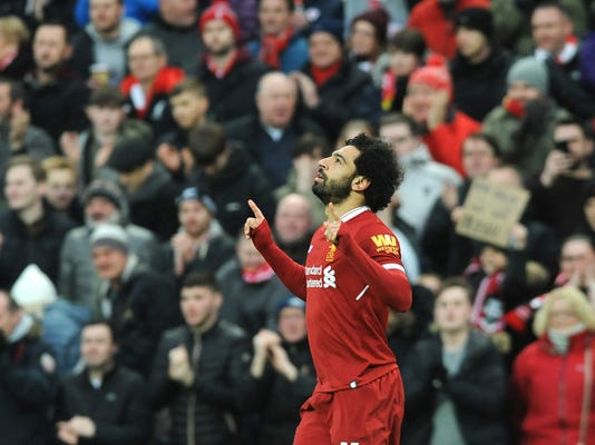 Liverpool's Mohamed Salah celebrates after scoring his side's first goal during the English Premier League soccer match between Liverpool and Tottenham Hotspur at Anfield in Liverpool, England, Sunday, Feb. 4, 2018. (AP Photo/Rui Vieira)
