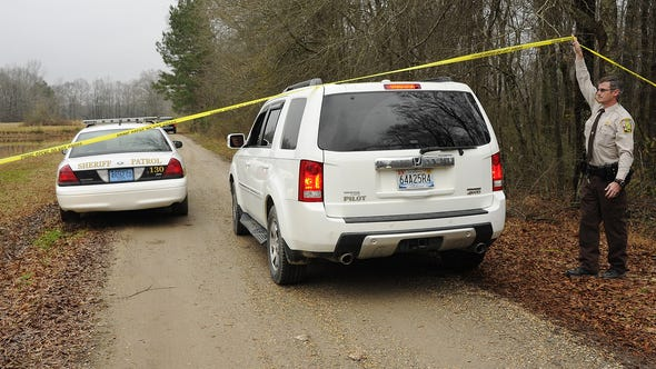 A Walker County sheriff's deputy lifts crime scene tape for investigators as National Transportation Safety Board officials continue to investigate the fatal crash of a small plane that was reported stolen near Jasper, Ala.