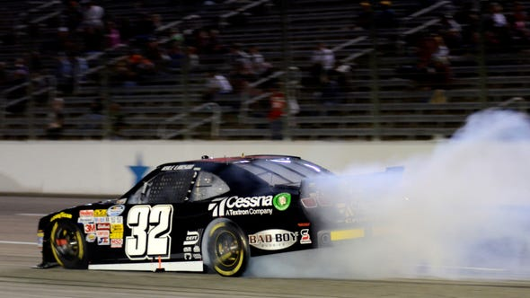 Driver Kyle Larson's car spews smoke as he attempts to control a spin into the front stretch during the NASCAR Nationwide series auto race at Texas Motor Speedway, Friday, April 12, 2013, in Fort Worth, Texas.