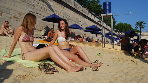Beachgoers soak up the sun by the Seine.