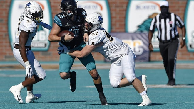 Coastal Carolina quarterback Grayson McCall (10) scrambles as Appalachian State's Caleb Spurlin (97) and Nick Hampton close in during the first half Saturday in Conway, S.C. Coastal Carolina won 34-23.