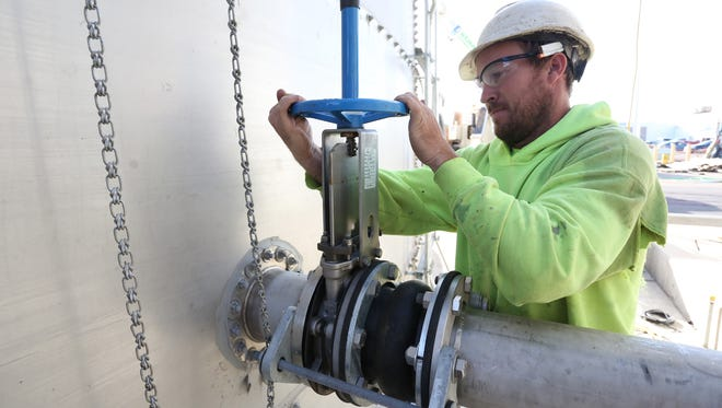 Supervisor for Staab Construction of Marshfield, Cliff Parker turns a valve as he lets more water into a tank at a water treatment plant consturction site at the Land O'Lakes cheese processing facility in Spencer, Wednesday, October 7, 2015. Parker is a graduate of the Mid-State Technical College (Wisconsin Rapids) carpentry apprenticeship program.
