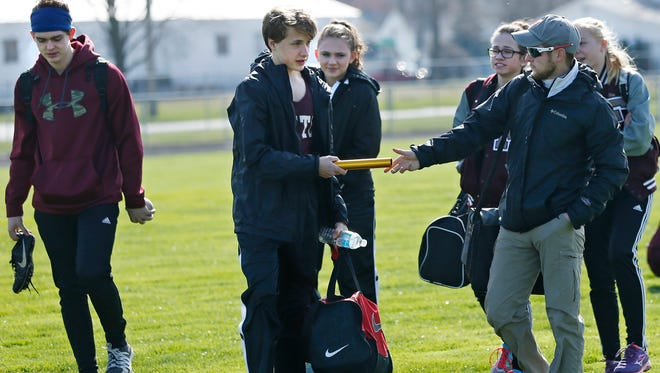 Faith Christian track coach Corey Spriggs passes a baton off to freshman Caden Tuinstra as the team arrives for track meet Tuesday, April 5, 2016, at North White High School in Monon. Faith Christian's meets are all on the road because they don't have a track at their school.