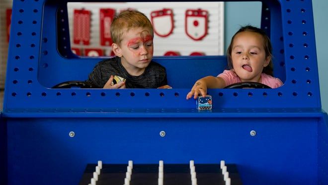 Caesar Bryant, 3, of Evansville (left) and Nora Mayes, 3, of Newburgh, apply wooden blocks to their vehicle in the Work Smart area at the Children's Museum of Evansville Wednesday afternoon.