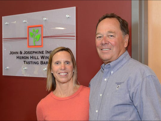 John and Josephine Ingle pose with the sign for the room bearing their name at the Finger Lakes Community College Viticulture and Wine Center during a reception on April 10.